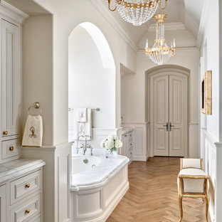 Design ideas for a mediterranean bathroom in Phoenix with recessed-panel cabinets, grey cabinets, a submerged bath, white walls, medium hardwood flooring, brown floors, white worktops, a built in vanity unit, a drop ceiling and wainscoting.