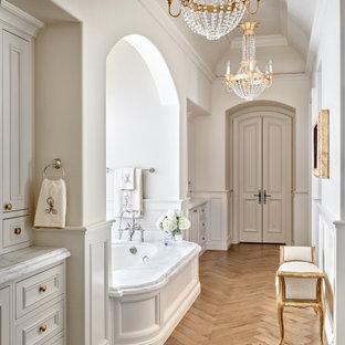 Cette photo montre une salle de bain méditerranéenne avec un placard avec porte à panneau encastré, des portes de placard grises, une baignoire encastrée, un mur blanc, un sol en bois brun, un sol marron, un plan de toilette blanc, meuble-lavabo encastré, un plafond décaissé et boiseries.