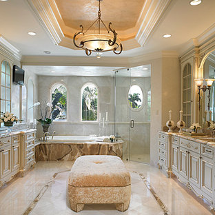 Large mediterranean ensuite bathroom in Miami with a submerged sink, raised-panel cabinets, beige cabinets, marble worktops, a built-in bath, a walk-in shower, a one-piece toilet, beige walls and marble flooring.