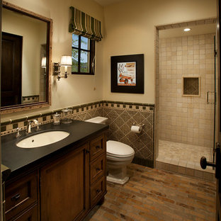 Inspiration for a mid-sized mediterranean 3/4 brick floor alcove shower remodel in Phoenix with an undermount sink, dark wood cabinets, beige walls and a two-piece toilet