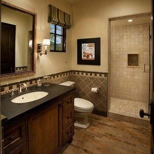 Ispirazione per una stanza da bagno con doccia mediterranea di medie dimensioni con lavabo sottopiano, ante in legno bruno, pareti beige, pavimento in mattoni, doccia alcova e WC a due pezzi