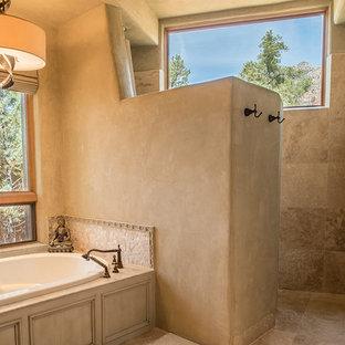 Réalisation d'une grand salle de bain principale sud-ouest américain avec une baignoire encastrée, une douche à l'italienne, un mur beige, un lavabo encastré, un placard avec porte à panneau encastré, des portes de placard en bois vieilli et un carrelage beige.