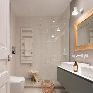 Foto de cuarto de baño con ducha, actual, de tamaño medio, con baldosas y/o azulejos blancos, baldosas y/o azulejos de cerámica, paredes beige, suelo beige, ducha abierta, armarios con paneles lisos, puertas de armario grises, ducha esquinera, sanitario de pared, lavabo sobreencimera y encimeras blancas