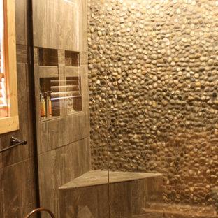Ejemplo de cuarto de baño principal, rural, grande, con armarios tipo mueble, puertas de armario de madera en tonos medios, bañera esquinera, ducha empotrada, baldosas y/o azulejos beige, baldosas y/o azulejos de travertino, paredes beige, suelo de travertino, lavabo bajoencimera, encimera de esteatita, suelo marrón y ducha con puerta con bisagras