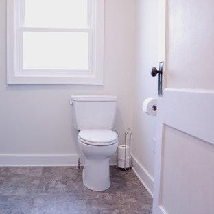 Modelo de cuarto de baño principal, clásico, pequeño, con armarios con paneles lisos, puertas de armario grises, ducha empotrada, sanitario de dos piezas, baldosas y/o azulejos grises, baldosas y/o azulejos de cemento, paredes grises, suelo vinílico, lavabo integrado, encimera de ónix, suelo gris, ducha con puerta con bisagras y encimeras grises
