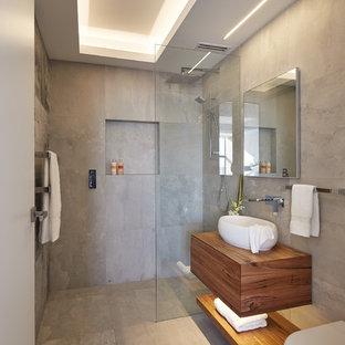 На фото: с высоким бюджетом ванные комнаты среднего размера в современном стиле с плоскими фасадами, фасадами цвета дерева среднего тона, душем без бортиков, инсталляцией, серой плиткой, душевой кабиной, настольной раковиной, столешницей из дерева, серым полом, открытым душем и коричневой столешницей