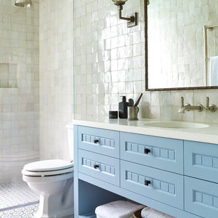Inspiration for a mid-sized beach style master bathroom in Melbourne with recessed-panel cabinets, blue cabinets, a corner shower, a one-piece toilet, white tile, mosaic tile, white walls, mosaic tile floors, a drop-in sink, engineered quartz benchtops, white floor and an open shower.