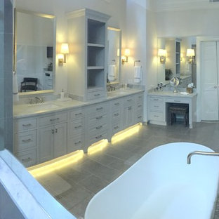 Bathroom - contemporary master gray tile and mosaic tile porcelain floor bathroom idea in Houston with recessed-panel cabinets, gray cabinets, a one-piece toilet, white walls, an undermount sink and marble countertops