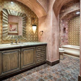 Diseño de cuarto de baño mediterráneo con lavabo bajoencimera, armarios con paneles con relieve, puertas de armario de madera en tonos medios, bañera empotrada, combinación de ducha y bañera y baldosas y/o azulejos multicolor