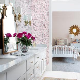 ヒューストンの巨大なトランジショナルスタイルのおしゃれな子供用バスルーム (白いキャビネット、ピンクの壁、セラミックタイルの床、オーバーカウンターシンク、珪岩の洗面台、白い床、白い洗面カウンター、洗面台2つ、造り付け洗面台、壁紙) の写真