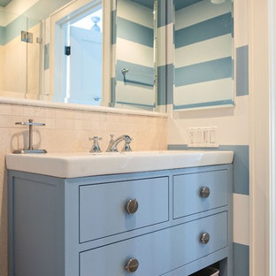 Photo of a small beach style family bathroom in Boston with beaded cabinets, blue cabinets, an alcove shower, beige tiles, stone tiles, blue walls, porcelain flooring, an integrated sink and solid surface worktops.