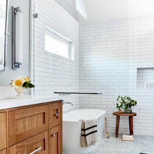 Inredning av ett klassiskt vit vitt badrum, med skåp i shakerstil, skåp i mellenmörkt trä, ett fristående badkar, våtrum, vit kakel, tunnelbanekakel, grå väggar, marmorgolv, ett undermonterad handfat och vitt golv