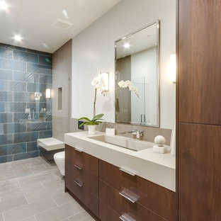 Modernes Duschbad mit flächenbündigen Schrankfronten, dunklen Holzschränken, Duschnische, weißer Wandfarbe, integriertem Waschbecken, grauem Boden, Falttür-Duschabtrennung und beiger Waschtischplatte in San Francisco