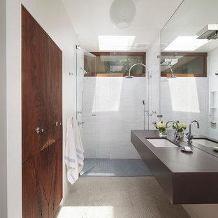 Inredning av ett retro badrum, med ett undermonterad handfat, en dusch i en alkov, vit kakel och betonggolv