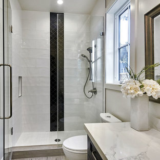 Mid-sized country 3/4 white tile and subway tile porcelain floor and gray floor alcove shower photo in San Francisco with shaker cabinets, black cabinets, a one-piece toilet, white walls, an undermount sink, engineered quartz countertops, a hinged shower door and white countertops