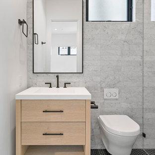 Modelo de cuarto de baño con ducha, minimalista, de tamaño medio, con armarios con paneles lisos, puertas de armario de madera clara, ducha empotrada, sanitario de pared, baldosas y/o azulejos grises, baldosas y/o azulejos de mármol, paredes grises, suelo de baldosas de porcelana, lavabo bajoencimera, encimera de acrílico, suelo negro y encimeras blancas