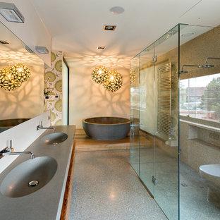 Idéer för att renovera ett stort funkis en-suite badrum, med ett integrerad handfat, ett fristående badkar, en kantlös dusch, en toalettstol med hel cisternkåpa, beige kakel, beige väggar, mosaik och betonggolv