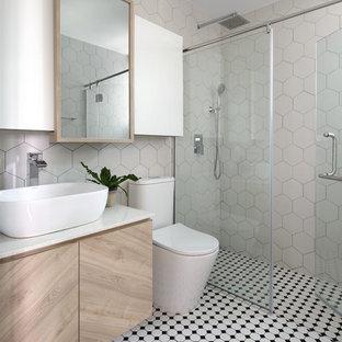 Foto di una stanza da bagno con doccia scandinava con ante lisce, ante in legno chiaro, doccia alcova, WC a due pezzi, piastrelle beige, pareti beige, lavabo a bacinella, pavimento multicolore, porta doccia a battente e top bianco