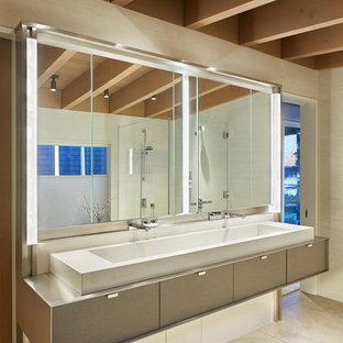 Пример оригинального дизайна: огромная главная ванная комната в стиле модернизм с плоскими фасадами, полновстраиваемой ванной, душем без бортиков, белой плиткой, керамогранитной плиткой, белыми стенами, бетонным полом, монолитной раковиной, столешницей из нержавеющей стали, серым полом, душем с распашными дверями и серой столешницей