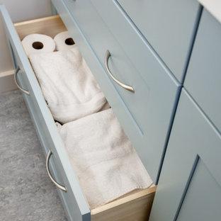 Стильный дизайн: маленькая ванная комната в стиле современная классика с фасадами в стиле шейкер, бирюзовыми фасадами, угловым душем, унитазом-моноблоком, серой плиткой, керамогранитной плиткой, белыми стенами, полом из линолеума, душевой кабиной, врезной раковиной, столешницей из искусственного кварца, серым полом, душем с распашными дверями, белой столешницей, нишей, тумбой под одну раковину и встроенной тумбой - последний тренд