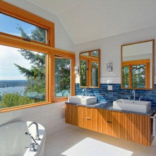 Inspiration för ett funkis badrum, med ett fristående handfat, ett hörnbadkar, släta luckor, skåp i mellenmörkt trä, bänkskiva i kvarts, blå kakel och glaskakel