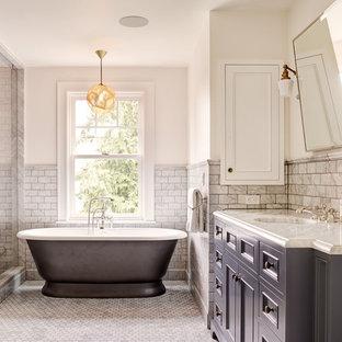 シアトルのトラディショナルスタイルのおしゃれなマスターバスルーム (落し込みパネル扉のキャビネット、グレーのキャビネット、置き型浴槽、白いタイル、大理石タイル、白い壁、大理石の床、アンダーカウンター洗面器、白い床) の写真