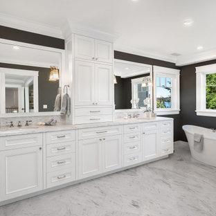 Maritim inredning av ett stort vit vitt en-suite badrum, med luckor med profilerade fronter, vita skåp, ett fristående badkar, en dusch i en alkov, en toalettstol med separat cisternkåpa, vit kakel, marmorkakel, grå väggar, marmorgolv, ett undermonterad handfat, marmorbänkskiva, vitt golv och dusch med gångjärnsdörr