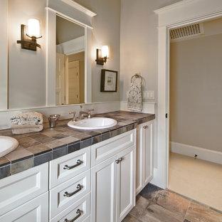 Esempio di una stanza da bagno tradizionale di medie dimensioni con lavabo da incasso, ante con riquadro incassato, ante bianche, top piastrellato, piastrelle beige, piastrelle in gres porcellanato e pareti grigie