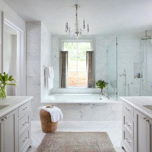 Modelo de cuarto de baño principal, clásico, con lavabo bajoencimera, armarios estilo shaker, puertas de armario grises, bañera encastrada sin remate, ducha esquinera, baldosas y/o azulejos blancos, paredes grises y baldosas y/o azulejos de piedra