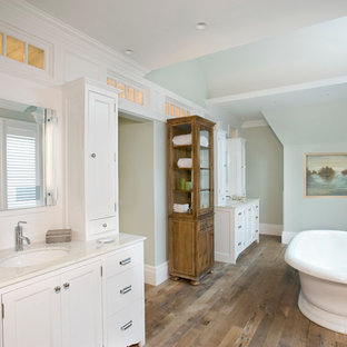 Example of a classic medium tone wood floor freestanding bathtub design in Boston with an undermount sink, shaker cabinets, white cabinets and green walls