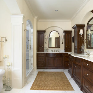 Esempio di una stanza da bagno tradizionale con lavabo sottopiano, ante con bugna sagomata, ante in legno bruno, top in marmo, doccia alcova, WC a due pezzi, piastrelle bianche, piastrelle in pietra e top bianco