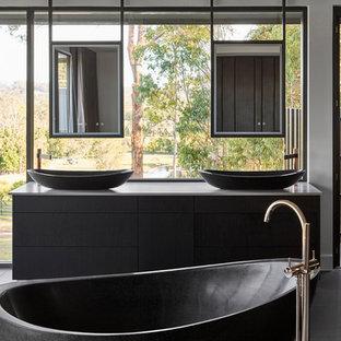 Diseño de cuarto de baño principal, minimalista, con armarios con paneles lisos, puertas de armario negras, bañera exenta, lavabo sobreencimera, suelo gris y encimeras grises