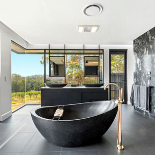 Photo of a contemporary bathroom in Sunshine Coast with flat-panel cabinets, black cabinets, a freestanding tub, black and white tile, stone slab, white walls, a vessel sink, grey floor and a double vanity.