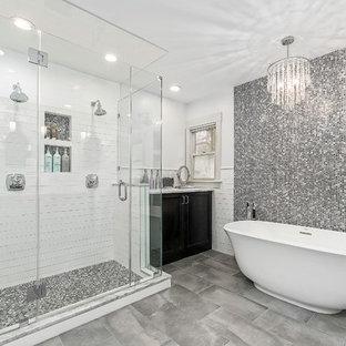 Inspiration för klassiska en-suite badrum, med luckor med infälld panel, svarta skåp, ett fristående badkar, en dubbeldusch, svart och vit kakel, grå kakel, vita väggar, grått golv, dusch med gångjärnsdörr, mosaik och klinkergolv i porslin