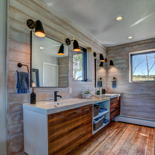 デンバーのカントリー風おしゃれなマスターバスルーム (フラットパネル扉のキャビネット、茶色いタイル、茶色い壁、木目調タイルの床、一体型シンク、茶色い床、洗面台2つ、フローティング洗面台、板張り壁) の写真