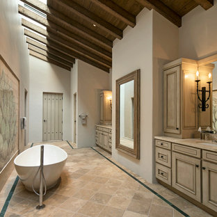 Tuscan master porcelain floor freestanding bathtub photo in Santa Barbara with raised-panel cabinets, light wood cabinets, beige walls and an undermount sink