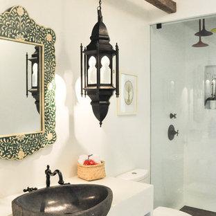 Diseño de cuarto de baño infantil, bohemio, pequeño, con armarios abiertos, puertas de armario blancas, ducha abierta, sanitario de una pieza, paredes blancas, suelo de cemento, lavabo sobreencimera, encimera de cemento y suelo blanco