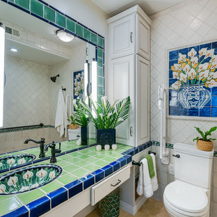 Photo of a small mediterranean ensuite bathroom in San Diego with raised-panel cabinets, white cabinets, a two-piece toilet, green tiles, terracotta tiles, white walls, porcelain flooring, a submerged sink and tiled worktops.