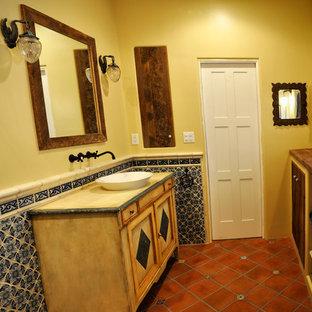 Esempio di una stanza da bagno con doccia stile americano di medie dimensioni con pareti gialle, pavimento in terracotta, lavabo a bacinella, pavimento rosso, ante con riquadro incassato, ante con finitura invecchiata, doccia alcova, top in legno e porta doccia a battente