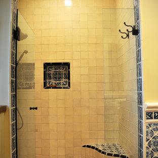 На фото: ванные комнаты среднего размера с фасадами с утопленной филенкой, искусственно-состаренными фасадами, душем в нише, желтыми стенами, полом из терракотовой плитки, душевой кабиной, настольной раковиной, столешницей из дерева, красным полом и душем с распашными дверями