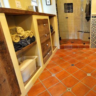 Réalisation d'une salle de bain sud-ouest américain de taille moyenne avec un placard avec porte à panneau encastré, des portes de placard en bois vieilli, un mur jaune, un sol en carreau de terre cuite, une vasque, un plan de toilette en bois, un sol rouge et une cabine de douche à porte battante.