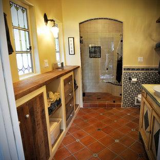 サンディエゴの中くらいのサンタフェスタイルのおしゃれなバスルーム (浴槽なし) (テラコッタタイルの床、ベッセル式洗面器、赤い床、落し込みパネル扉のキャビネット、ヴィンテージ仕上げキャビネット、アルコーブ型シャワー、黄色い壁、木製洗面台、開き戸のシャワー) の写真