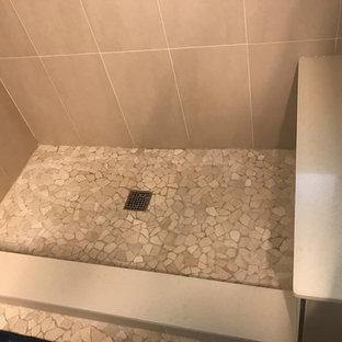 Mittelgroßes Modernes Duschbad mit flächenbündigen Schrankfronten, beigen Schränken, Wandtoilette mit Spülkasten, beigefarbenen Fliesen, Porzellanfliesen, beiger Wandfarbe, Kiesel-Bodenfliesen, Unterbauwaschbecken, Quarzwerkstein-Waschtisch, beigem Boden und Falttür-Duschabtrennung in Jacksonville