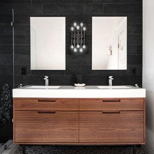 Idéer för att renovera ett funkis badrum, med ett integrerad handfat, släta luckor, skåp i mellenmörkt trä, svart kakel, svart och vit kakel och svarta väggar