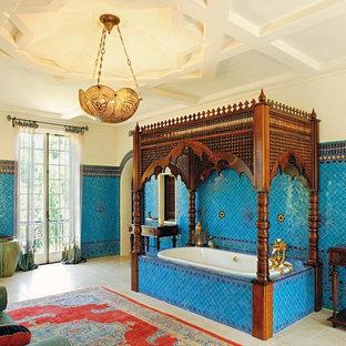 Idee per una stanza da bagno mediterranea con consolle stile comò, ante in legno bruno, vasca da incasso e piastrelle blu