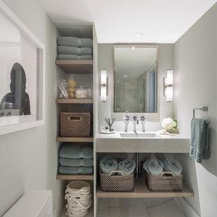 Diseño de cuarto de baño principal, actual, de tamaño medio, con armarios abiertos, puertas de armario de madera clara, baldosas y/o azulejos blancos, baldosas y/o azulejos de piedra, paredes grises, suelo de mármol, sanitario de una pieza, lavabo integrado y encimera de cemento