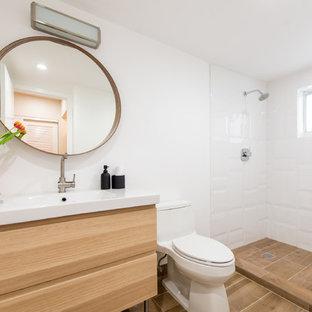 Diseño de cuarto de baño con ducha, moderno, grande, con armarios con paneles lisos, puertas de armario de madera clara, ducha abierta, sanitario de una pieza, baldosas y/o azulejos de porcelana, paredes blancas, suelo de madera clara, lavabo de seno grande y encimera de azulejos