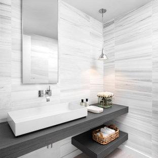 Modelo de cuarto de baño principal, actual, de tamaño medio, con armarios abiertos, baldosas y/o azulejos grises, baldosas y/o azulejos blancos, suelo de madera clara, lavabo sobreencimera, puertas de armario grises, baldosas y/o azulejos de piedra, paredes grises, encimera de madera y suelo marrón