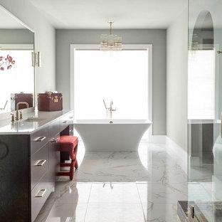 Modern inredning av ett en-suite badrum, med släta luckor, skåp i mörkt trä, bänkskiva i återvunnet glas, ett fristående badkar, beige väggar, marmorgolv, ett undermonterad handfat, vit kakel och stenkakel