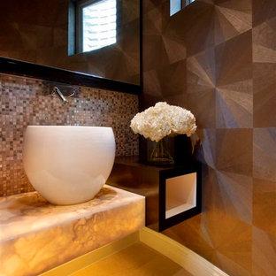 Modelo de cuarto de baño con ducha, minimalista, pequeño, con armarios con paneles lisos, puertas de armario de madera en tonos medios, baldosas y/o azulejos beige, losas de piedra, paredes marrones, suelo de piedra caliza, lavabo sobreencimera y encimera de ónix